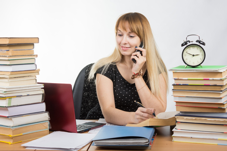 understands: A student preparing for exams and talking on the phone Stock Photo