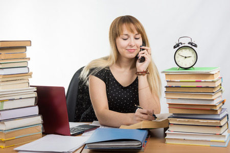 Student discusses by phone the paragraph in the textbook Stock Photo