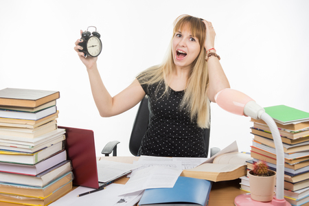 A student with an alarm clock in hands understand that slept exam Stock Photo