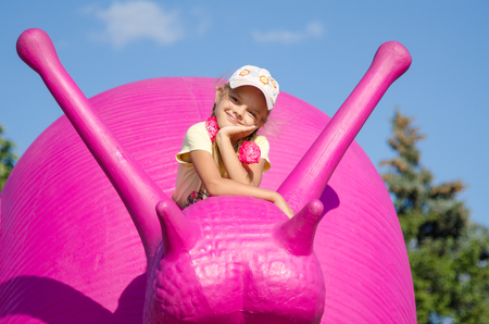 enea: Moscow, Russia August 10, 2015: Six-year girl on a pink snail, exhibit ENEA in Moscow