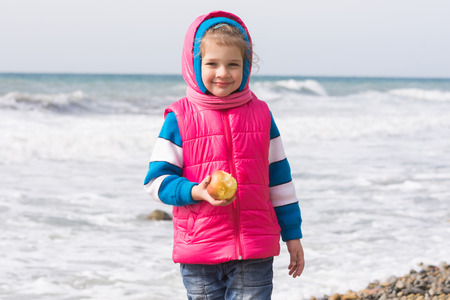 five year: Portrait of a five year old girl with an apple on the beach
