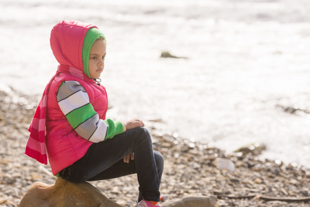 Thoughtful girl sitting on a rock on the stony beach of the sea and looks into the distance