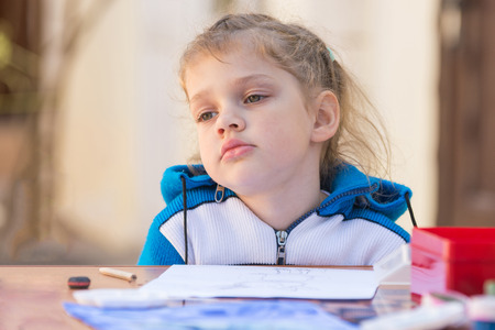 Frustrated girl sitting at a table in the yard and sad looks nowhere Stock Photo