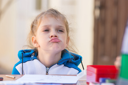 puffed cheeks: Frustrated girl sitting at a table in the courtyard of the house and looking cocky Stock Photo