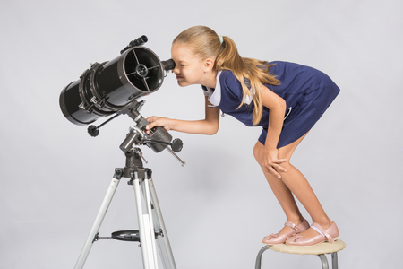 spying: Seven-year girl standing on a chair and looks ridiculous in the eyepiece of the telescope reflector