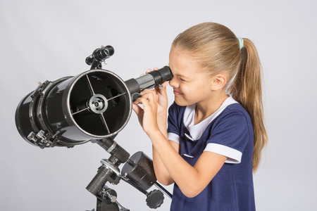reflector: Seven-year girl squinting with interest looks in a reflector telescope