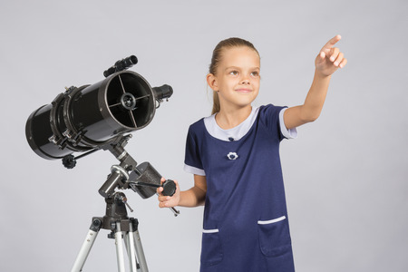 ufology: The young astronomer shows the starry sky while standing at the telescope Stock Photo