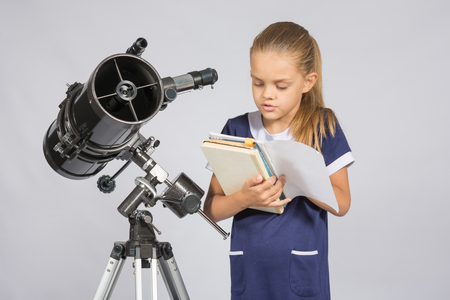 astronomer: Schoolgirl reading a textbook while standing astronomer at the telescope