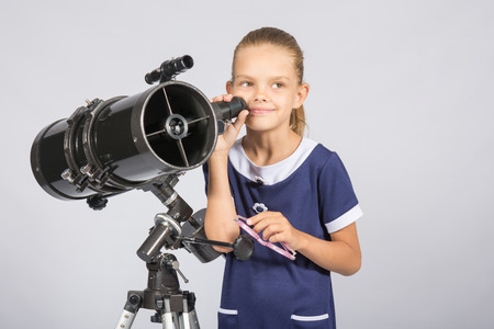 Seven-year girl standing next to a reflector telescope and looks mysteriously into the sky Stock Photo