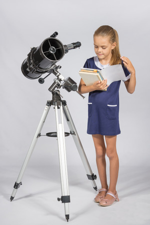 Schoolgirl leafing through a textbook while standing at the telescope Stock Photo