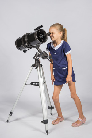 an eyepiece: Young funny astronomer looks through the eyepiece of the telescope Stock Photo