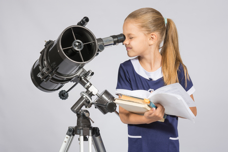 textbooks: School girl looking through a telescope standing with textbooks