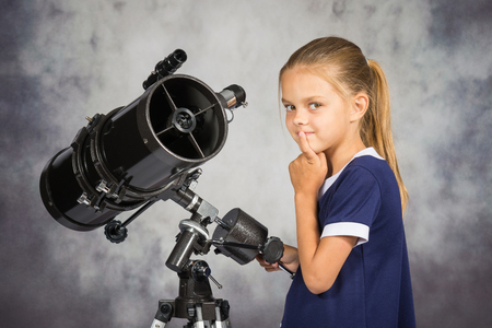 Seven-year girl thoughtfully looks in the picture, standing at the telescope Stock Photo