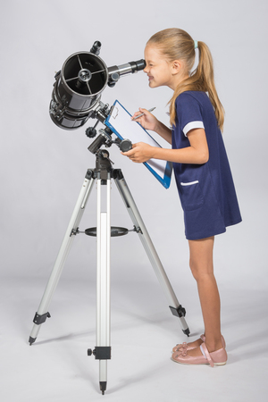 observations: The young astronomer happy to look through the telescope recording observations