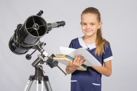 astronomer: Schoolgirl astronomer leafing through books standing at the telescope Stock Photo