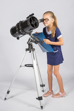 peers: The young astronomer in glasses with interest peers into the eyepiece of the telescope