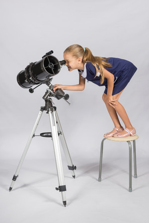 The young astronomer standing on a chair and funny looking in a telescope eyepiece Stock Photo