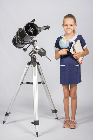 astronomer: Schoolgirl astronomer is a telescope with a globe and books in the hands