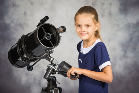 looked: Seven-year girl adjusts the telescope and looked into the frame