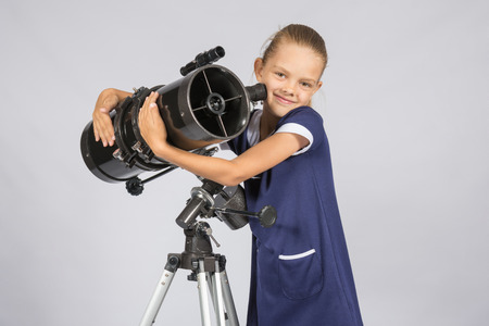 ufology: Seven-year girl hugging her given reflector telescope Stock Photo