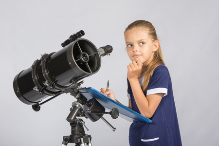 observations: Seven-year girl thoughtful looking at the sky, making the recording of observations in the telescope Stock Photo