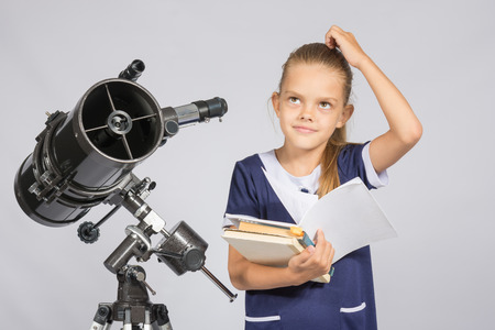 looked: Schoolgirl wondered and looked up to by reading a textbook while standing at the telescope