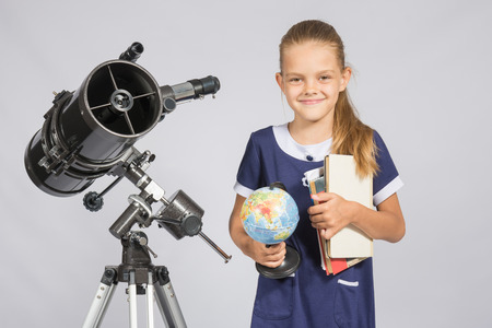 astronomer: Girl astronomer is a telescope with a globe and books in the hands