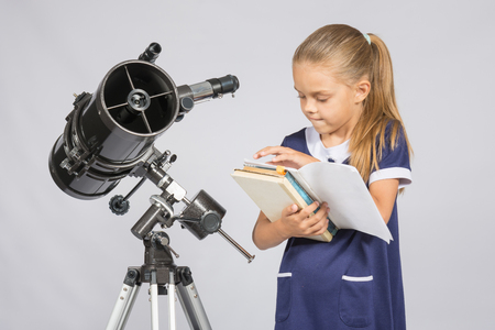 Schoolgirl astronomer leafing through books to find the right information at the stand of the telescope