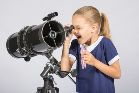 reflector: Seven-year girl with interest and mouth open looking into the reflector telescope and looks at the sky
