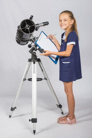 Happy girl astronomer looks happy in the picture standing next to the telescope Stock Photo