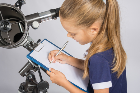 astronomer: Girl astronomer writes on a sheet of paper of a starry sky with your telescope Stock Photo
