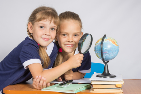 intrigued: Two schoolgirls looking at globe through a magnifying glass Stock Photo