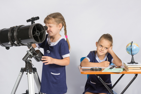 expects: Girl astronomer looks through the eyepiece of the telescope, the other girl thinking waiting for the results of observations Stock Photo