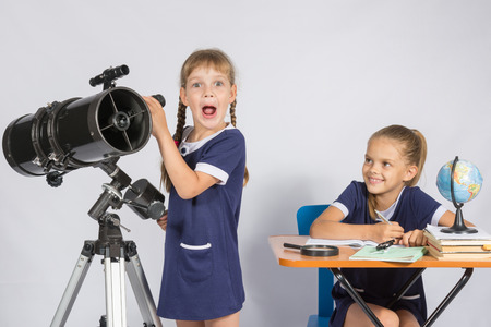 expects: Girl surprised astronomer observing through a telescope, the other girl looked at her Stock Photo