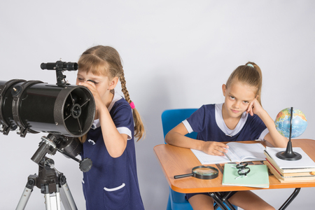 expects: Girl astronomer looks at the sky through a telescope, the other girl is sitting at the table