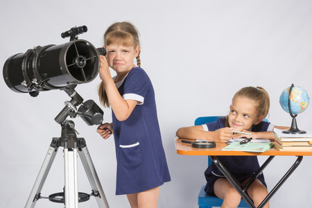 mocking: The girl was upset he did not see in the telescope, the other girl mocking her Stock Photo
