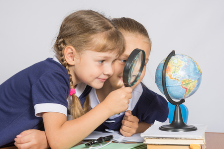 intrigued: Two girls girlfriends looking at globe through a magnifying glass