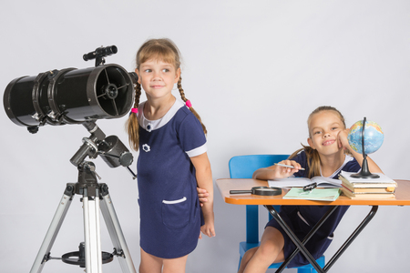 expects: Girl astronomer looks at the sky, the other girl sitting happily at the table Stock Photo