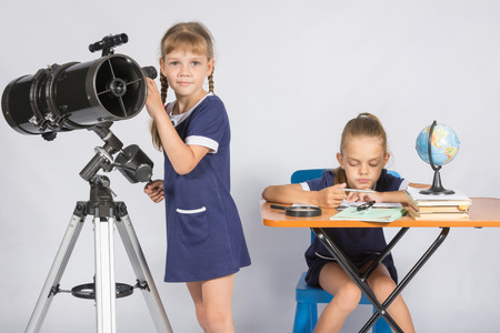 observations: Girl watches in the telescope, the other girl is waiting for the results of observations Stock Photo