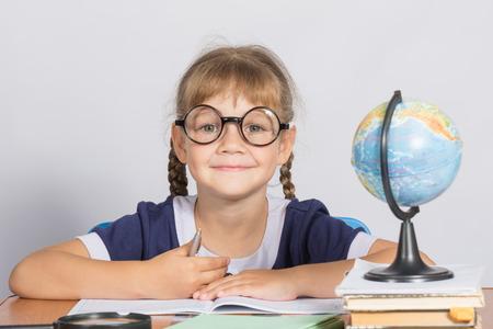 grader: Happy girl first grader sits at a table Stock Photo