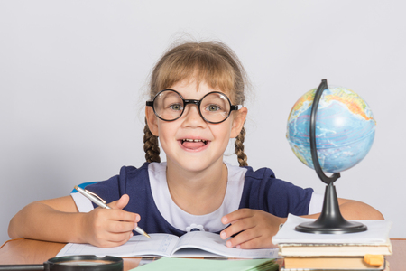 grader: Happy first grader sits at a table in the classroom, with his mouth open in pleasure Stock Photo