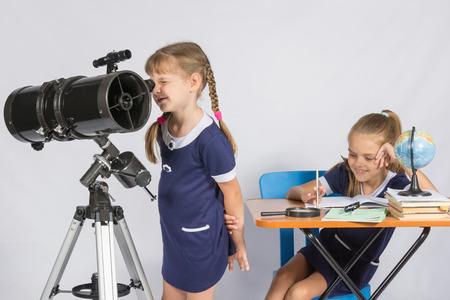Chica astrónomo mira a través del ocular del telescopio, y la otra muchacha que se sienta feliz en la tabla Foto de archivo