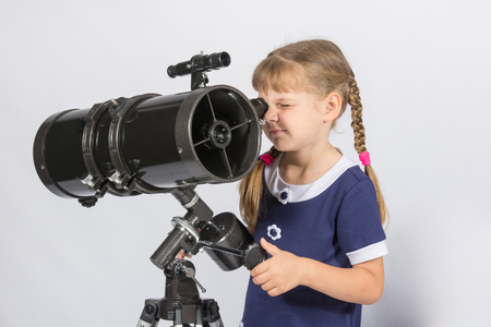astronomer: Girl amateur astronomer sets up a telescope for observing the starry sky