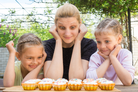 Mother and two daughters with a good appetite and big eyes looking at easter cupcakes Stock Photo