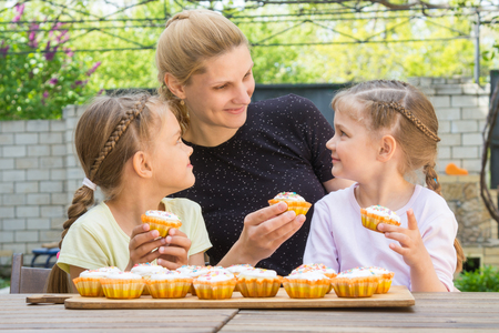homemaker: Mother and two daughters sitting at the table with Easter cupcakes in his hands Stock Photo