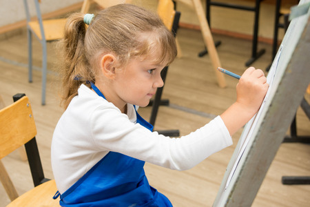 additional training: Five-year girl paints on an easel in the drawing lesson Stock Photo