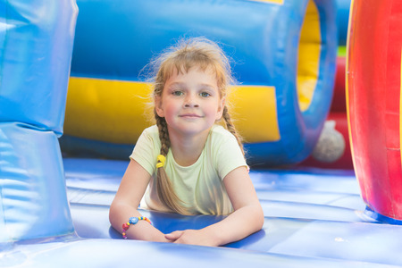 five year old: Disheveled five year old girl is playing on a big inflatable trampoline Stock Photo