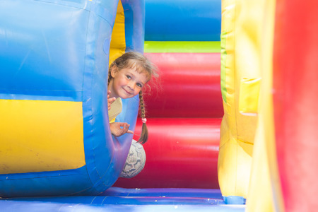 'hide out': Happy little girl got out of the inflatable soft barrel while playing on the trampoline