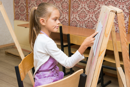 additional training: Girl artist with a smile look in the picture on the drawing lesson