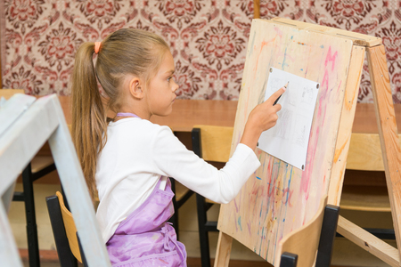 Girl paints on an easel in the drawing lesson Stock Photo